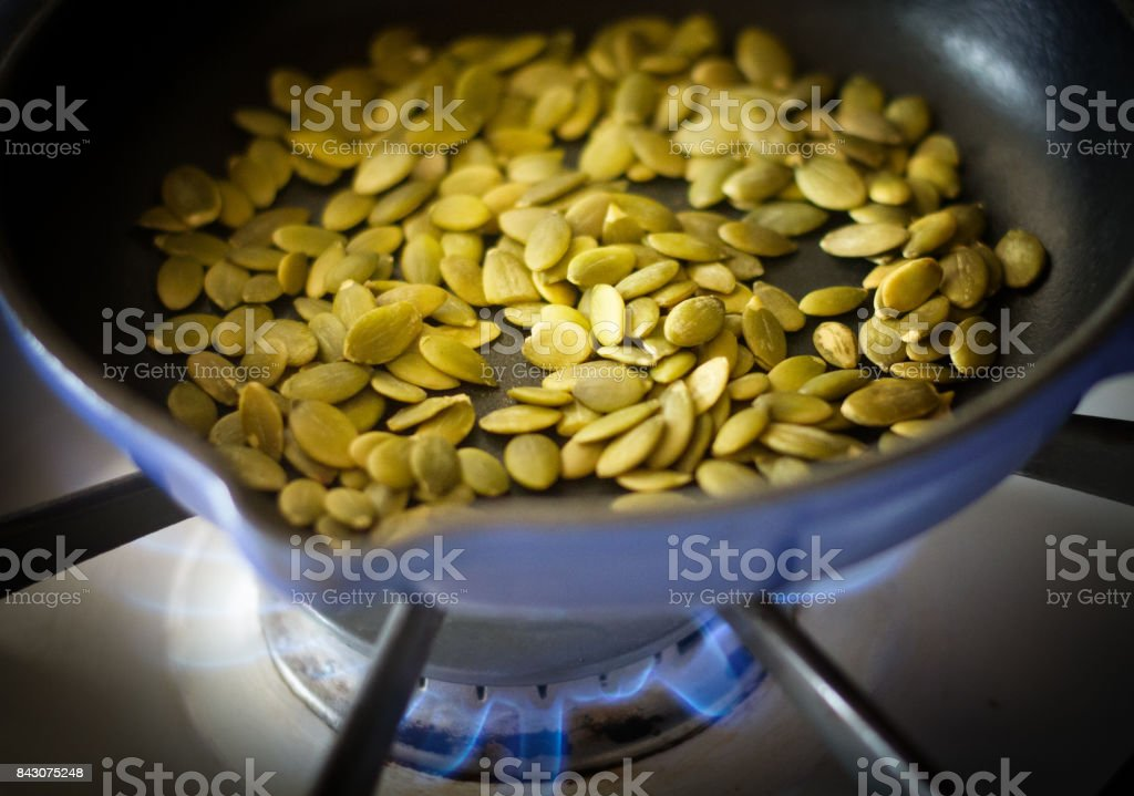 Toasting Pumpkin Seeds/Pepitas on Stovetop (Close-Up) stock photo