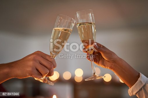 Closeup shot of an unidentifiable couple toasting with glasses of wine