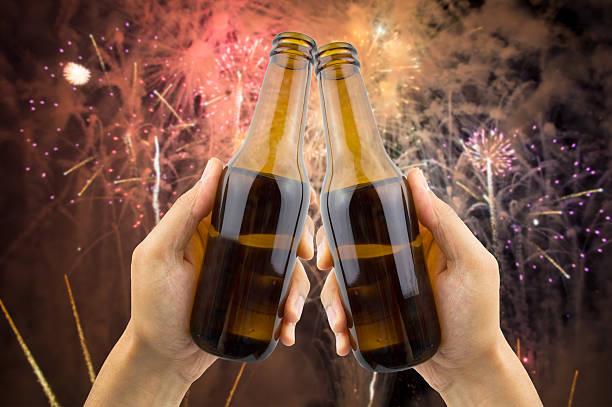 anstoßen mit bier an der party-nacht - frohes neues jahr stock-fotos und bilder