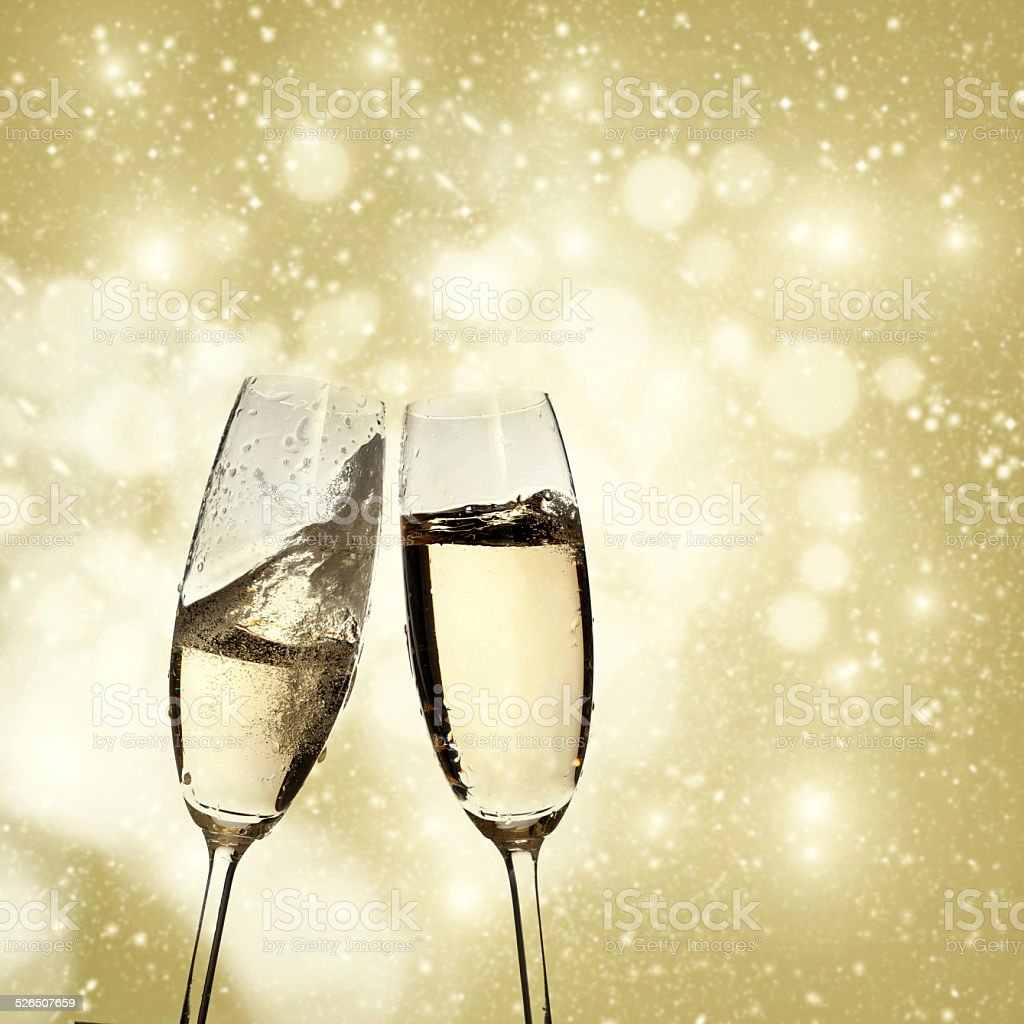 https://media.istockphoto.com/photos/toasting-with-champagne-glasses-on-sparkling-holiday-background-picture-id526507659