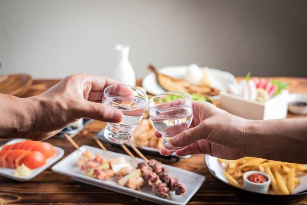 toasting with japanese sake and izakaya popular plates stock photo