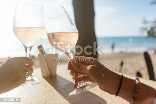 Close-up of friends toasting with rose wine