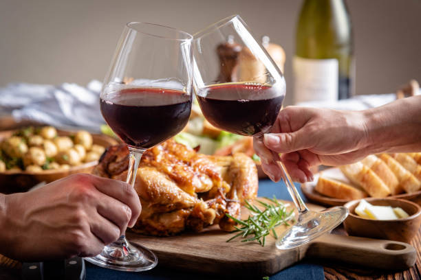 toasting with wine glasses in front of chicken dinner stock photo