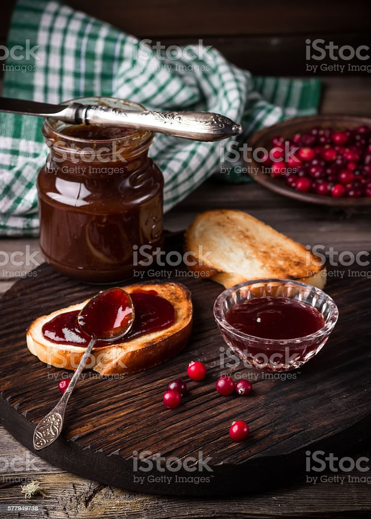 Toasts, jam and cowberry on dark cutting board. stock photo