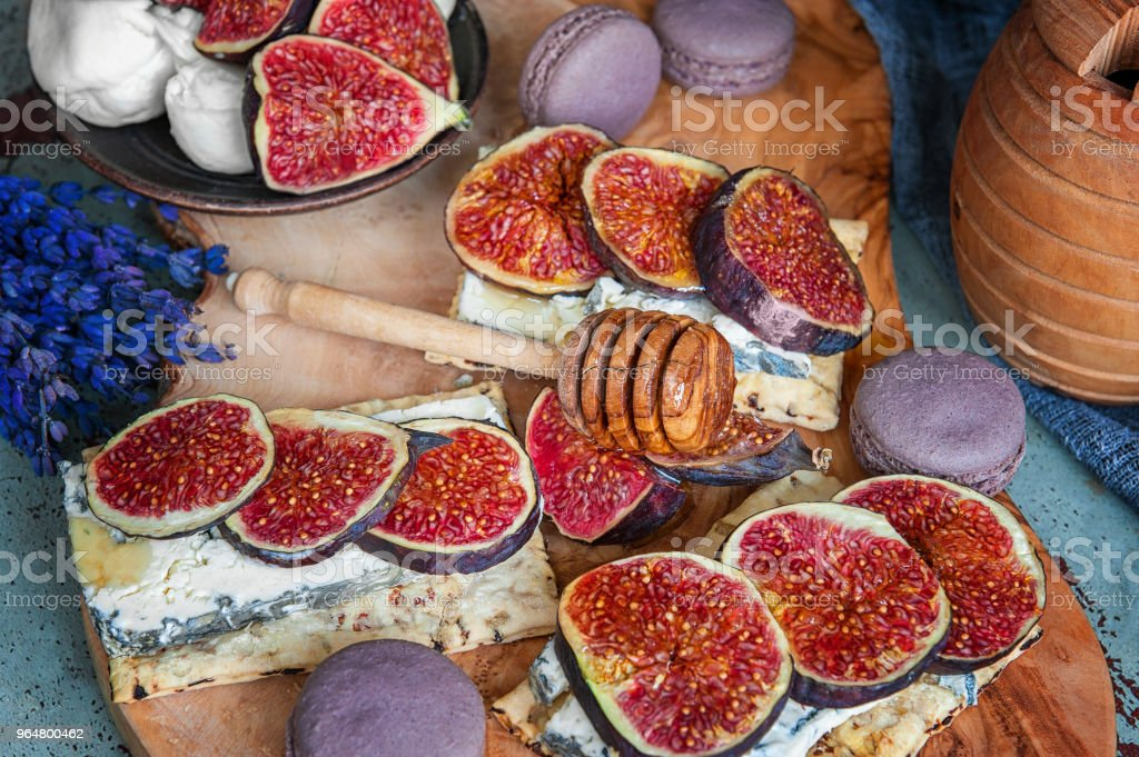 Toasts of cheese, figs and honey on whole-grain crispy bread. Close up royalty-free stock photo