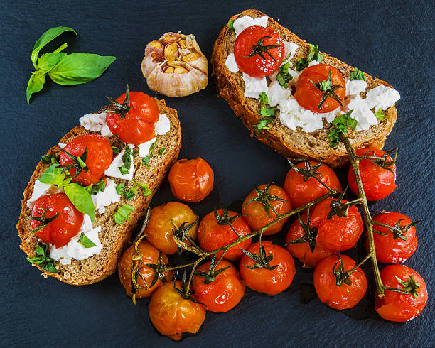 toasts with feta cheese and small cherry tomatoes, top view - ofengemüse mit feta stock-fotos und bilder