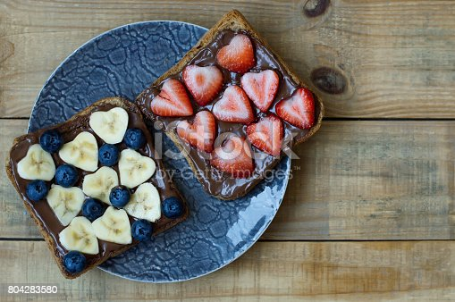 640978994 istock photo Toasts with heart shaped strawberry and banana, blueberry, chocolate cream 804283580