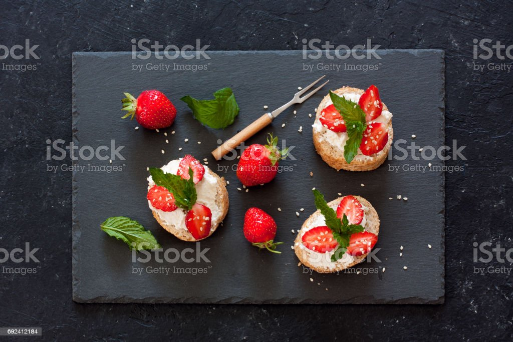 Toasts with oat  bread, ricotta and fresh strawberries stock photo