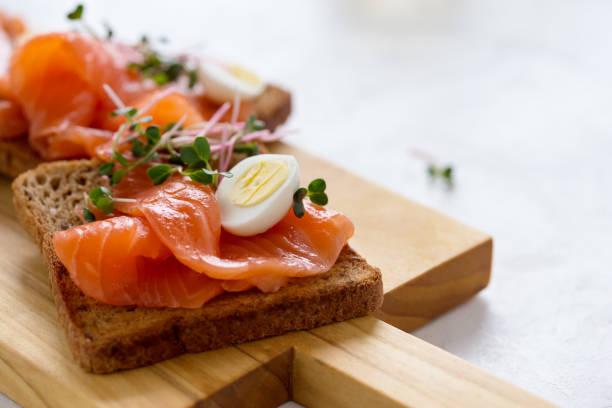 toast mit geräuchertem lachs, wachtelei und radieschen sprossen - pökeln stock-fotos und bilder