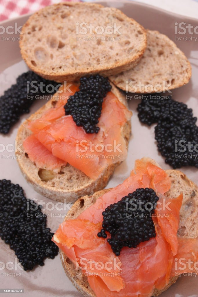 Toasts with smoked trout and lump eggs stock photo