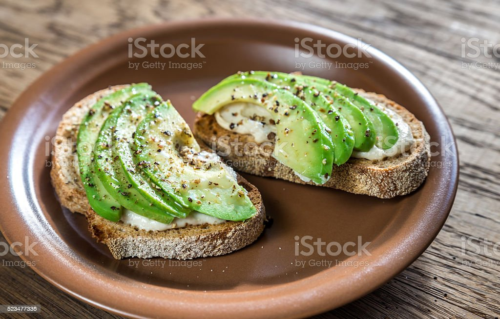 Toasts with tahini sauce and sliced avocado stock photo