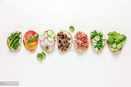 Culinary background with assortment of toasts lying in line, view from above, blank space for a text