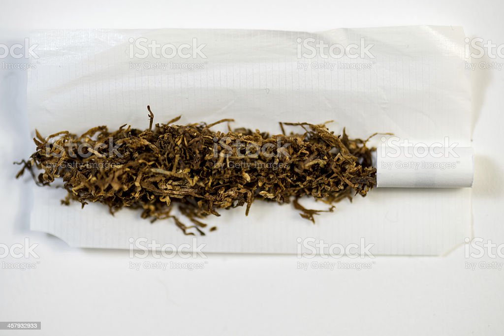 tobacco and filter on a rolling paper stock photo