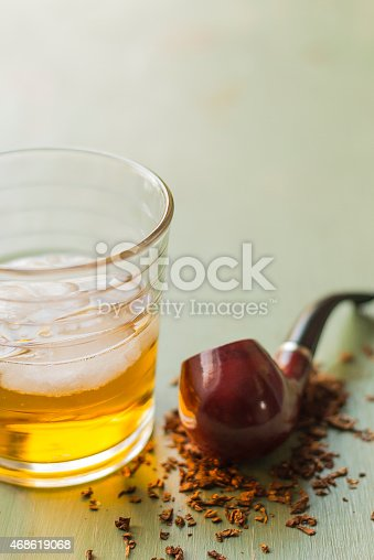 Tobacco pipe on rustic warn green wood surface with spilled natural tobacco and a glass of whisky on the rocks