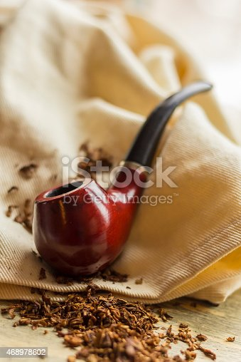 Tobacco pipe on rustic warn wood surface with spilled natural tobacco