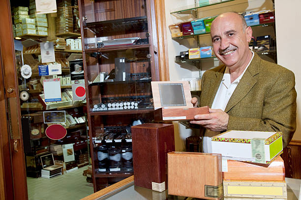 Tobacco shop worker Portrait of a happy owner showing cigar boxes in store armenian ethnicity stock pictures, royalty-free photos & images