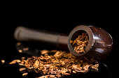 Tobacco Smoking pipe and tobacco spilled on a reflective glass surface, low key black background