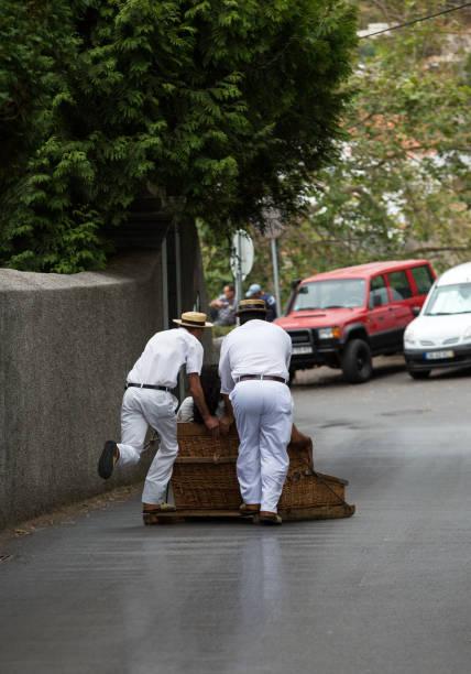 Coureurs de luge se déplaçant luge canne traditionnelle descente dans les rues de Funchal. - Photo