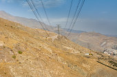 istock Tochal mountain with electricty transmission power cable in autumn against blue sky, Tehran, Iran. Tochal is a popular recreational region for Tehran's residents 1293387934