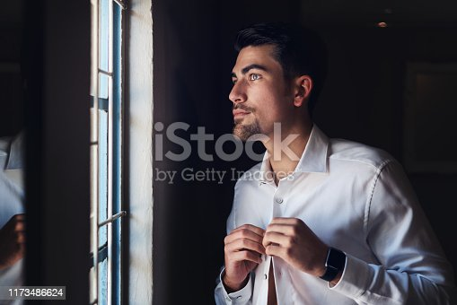 Shot of a handsome young man getting dressed on his wedding day