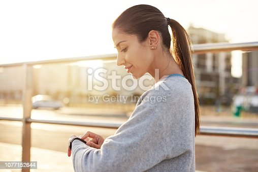 Shot of a sporty young woman checking her watch while exercising outdoors