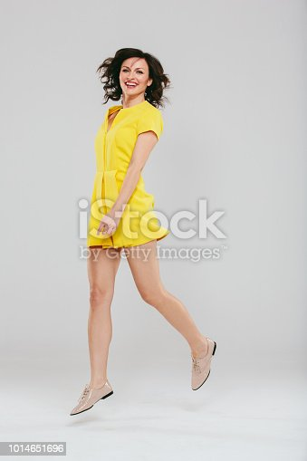Studio portrait of an attractive woman in a yellow dress posing against a gray background