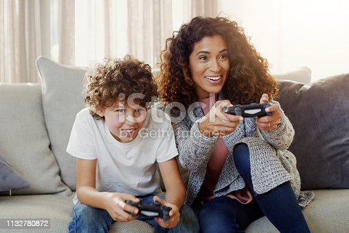 Shot of a young mother and her son playing video games together at home