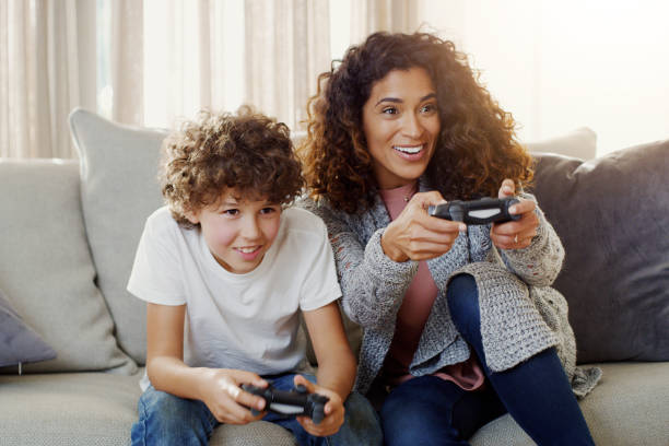 Today is game day with my little champ Shot of a young mother and her son playing video games together at home computer games stock pictures, royalty-free photos & images