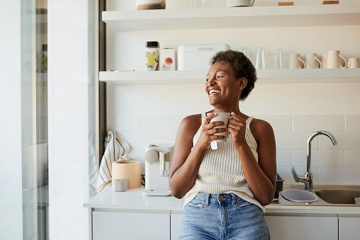 Shot of a young woman having a warm beverage during a relaxing day at home