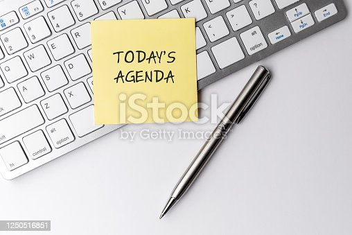 Today's agenda text on sticky note with computer keyboard and pen