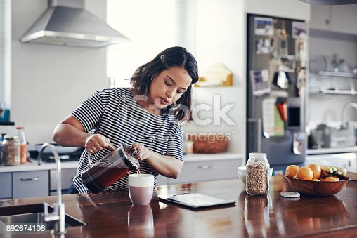 Shot of an attractive young woman drinking coffee while using a digital tablet at home