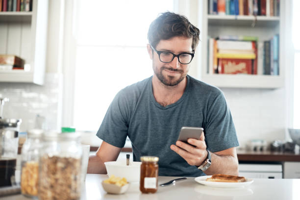 Today's forecast? It's going to be a great day Shot of a young man using a mobile phone while having breakfast in the kitchen at home smirking stock pictures, royalty-free photos & images
