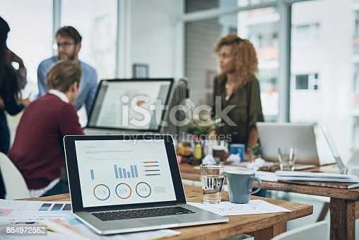 Closeup shot of a laptop with graphs on the screen and a team working in the background