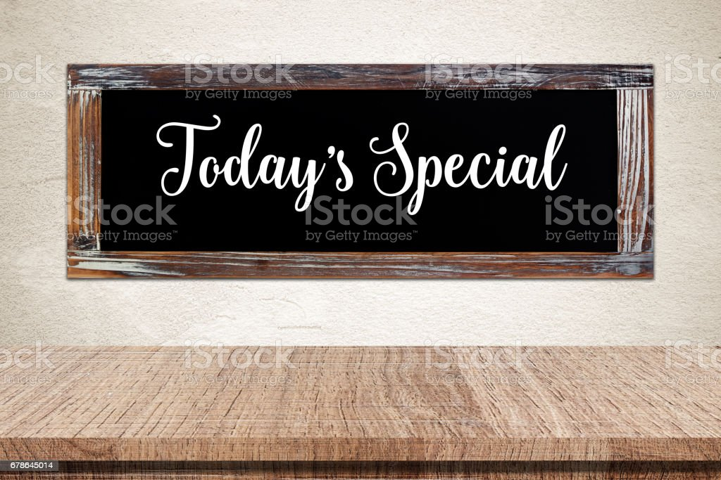 Today's special on vintage chalk board over empty wood table background, product and food display montage, template – Foto