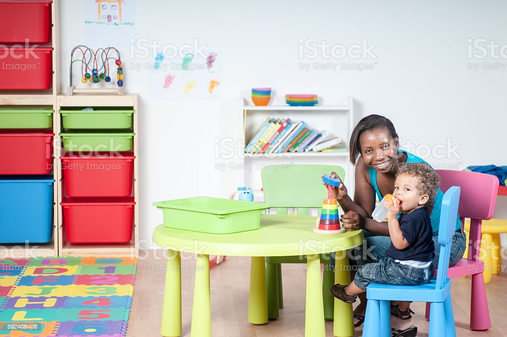 Toddler and Carer in the Nursery stock photo