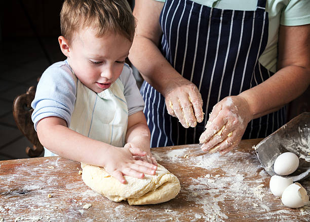 A toddler attempting to knead dough Little boy making bread with his grandma. baking bread stock pictures, royalty-free photos & images