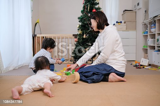 954356678 istock photo Toddler, baby and mother playing together with toy at Christmas 1084347784