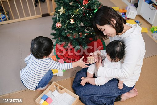954356678 istock photo Toddler, baby and mother playing together with toy at Christmas 1084347786
