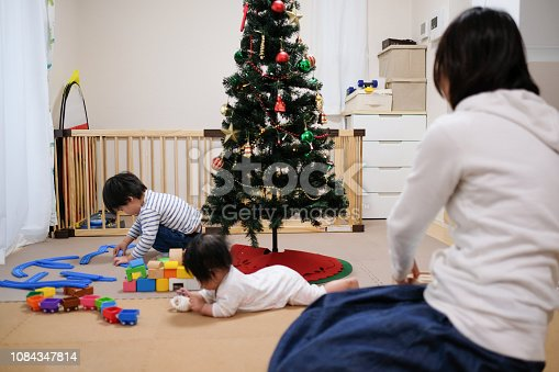 954356678 istock photo Toddler, baby and mother playing together with toy at Christmas 1084347814
