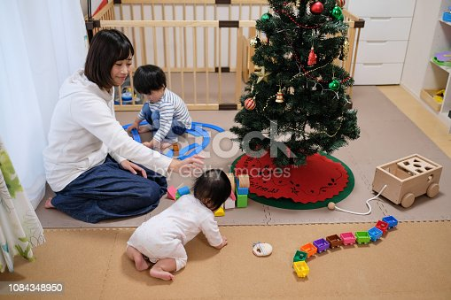 954356678 istock photo Toddler, baby and mother playing together with toy at Christmas 1084348950