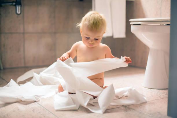 kleinkind baby boy, zerreißen mit toilettenpapier im bad - anti unordnung stock-fotos und bilder