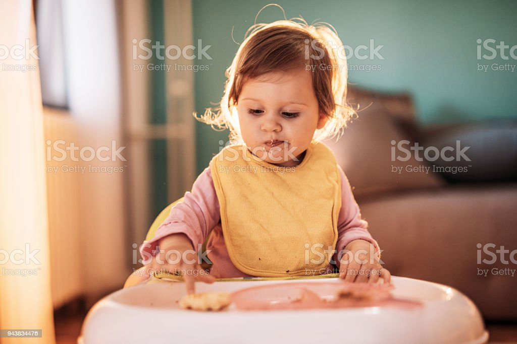 Toddler baby girl doesn't want to eat her food stock photo