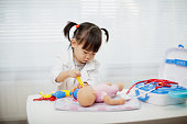 Toddler baby girl pretend playing as doctor at home