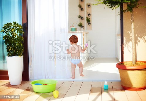 istock toddler baby walking away at warm sunny day at home 922531044