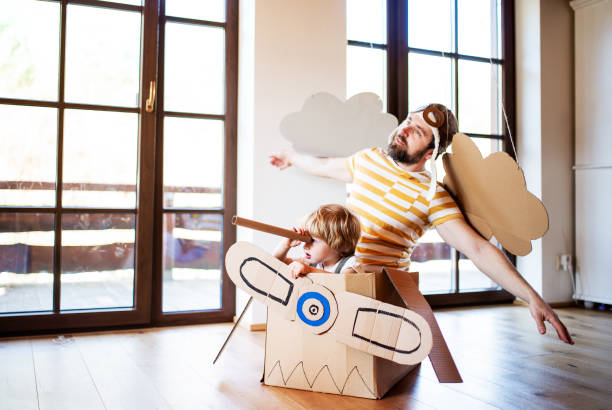 A toddler boy and father with carton plane playing indoors at home, flying concept. stock photo
