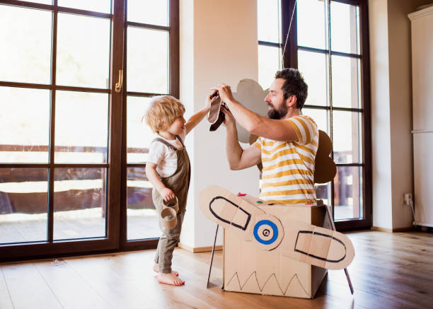 Ein todkranischer Junge und Vater mit Kartonflugzeug, das drinnen zu Hause spielt, fliegendes Konzept. – Foto