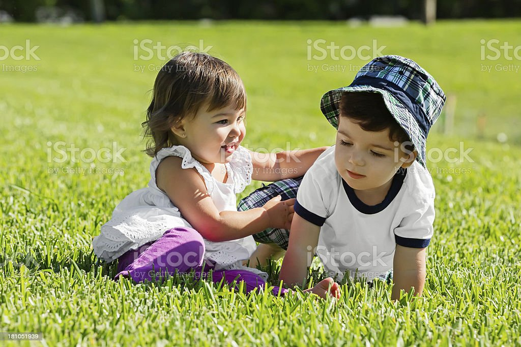 Toddler boy and girl twins playing stock photo