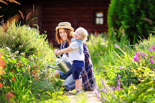toddler boy and his mother watering plants in the garden - lebensblume stock-fotos und bilder