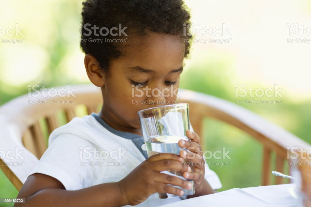 Toddler boy drinking a glass of water stock photo