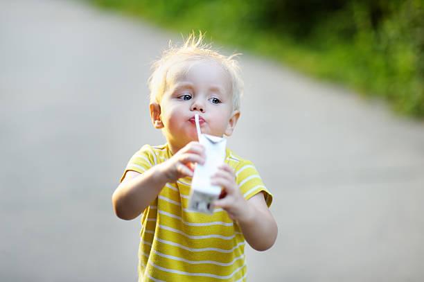 kleinkind – junge trinkt milch und saft - innocent saft stock-fotos und bilder